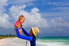 Father and little daughter having fun on the beach Stock Images