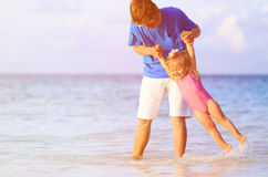 Father and little daughter having fun on beach Stock Photos