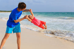 Father and little daughter having fun on beach Stock Images