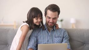 Father and daughter having fun listening music online use computer