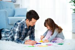 Father and little daughter having quality family time together at home. dad with girl lying on warm floor drawing with colorful stock photo