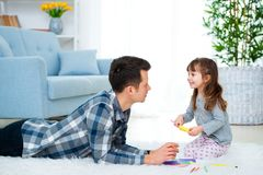 Father and little daughter having quality family time together at home. dad with girl lying on warm floor drawing with colorful royalty free stock image