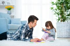 Father and little daughter having quality family time together at home. dad with girl lying on warm floor drawing with colorful stock images