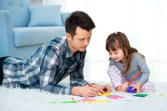 Father and little daughter having quality family time together at home. dad with girl lying on warm floor drawing with colorful stock image