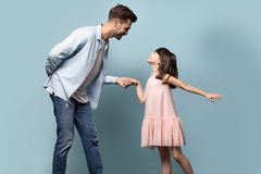 Father and little daughter holding hands dancing waltz studio shot stock photography