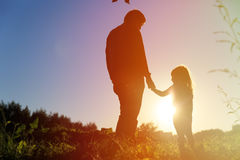 Father and little daughter holding hands at sunset sky stock photo
