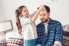 Father and little daughter at home sitting girl making hairstyle for man joyful royalty free stock photography