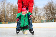 Father and little daughter learning to skate in winter Stock Photos