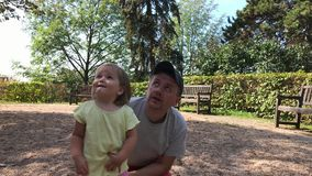 Father and little daughter look to sky in summer park in day