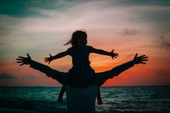Father and little daughter play at sunset sky. On beach royalty free stock images