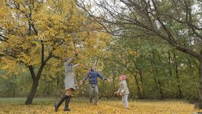 Daddy turns child in autumn park. dad twirling a child on a background of yellow leaves Royalty Free Stock Images