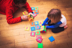 Father and little daughter playing with puzzle, early education Stock Photos