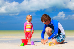 Father and little daughter playing with sand on Royalty Free Stock Images