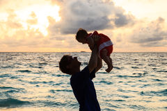 Father and little daughter playing on sunset beach Royalty Free Stock Photography