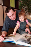 Father and little daughter reads book royalty free stock photos