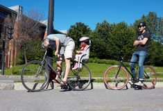 Father and little daughter riding a bike and another male biker waiting at the traffic lights in Montreal, Quebec, Canada stock photos