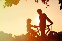 Father and little daughter riding bike at sunset Royalty Free Stock Photos