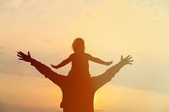 Father and little daughter on shoulders play at sunset sky Royalty Free Stock Images