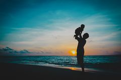 Father and little daughter silhouettes play at sunset. Beach royalty free stock image