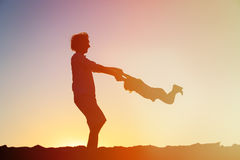 Father and little daughter silhouettes play at sunset Stock Photography