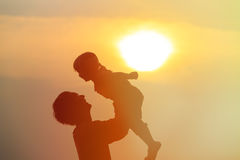 Father and little daughter silhouettes play at sunset Stock Images