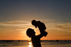Father and little daughter silhouettes on sunset beach Stock Photography