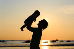 Father and little daughter silhouettes on sunset beach Royalty Free Stock Photography