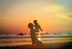 Father and little daughter silhouettes on sunset beach Stock Photos