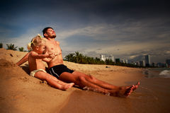father and little daughter sit and play on sand beach Royalty Free Stock Photo
