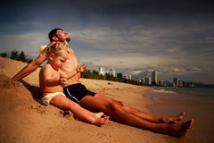 Father and little daughter sit and play on sand beach Royalty Free Stock Photos