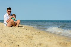 A father with a little daughter sits on the beach at the background of the sea stock image