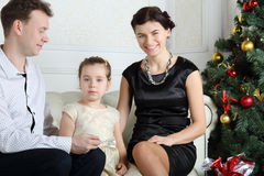 Father, little daughter and smiling mother sit on sofa Royalty Free Stock Photos
