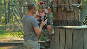 Father with little daughter spend leisure time in rope park stock video footage