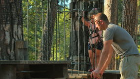 Father and little daughter spends leisure time in rope park together stock video