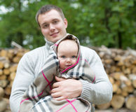 The father and the little daughter stand against wooden logs. The little daughter is wrapped up in a blanket Stock Photos