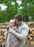 The father and the little daughter stand against wooden logs. The little daughter is wrapped up in a blanket royalty free stock photos