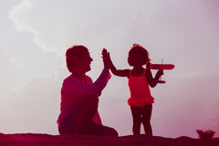 Father and little daughter with toy plane at sunset Stock Photography