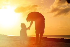 Father and little daughter walking on beach at Royalty Free Stock Photo