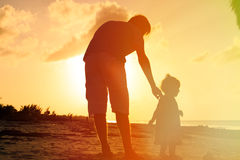 Father and little daughter walking on beach at Stock Photos