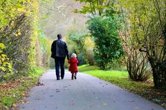 Father and little daughter walking in the park Stock Photo