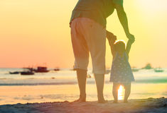 Father and little daughter walking on sunset beach Stock Photography