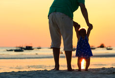 Father and little daughter walking on sunset beach Royalty Free Stock Photo