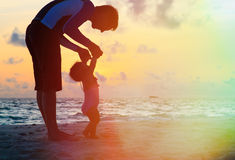 Father and little daughter walking on sunset beach Royalty Free Stock Images