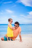 Father and little daughter on white beach Stock Photos
