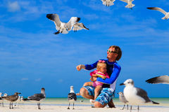 Father and little daugther feeding seagulls on the Stock Image