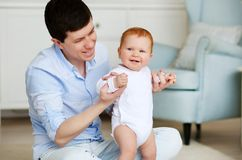 Father and little dauther. Baby taking first steps with father help in home interior. Father and little dauther. Baby taking first steps with father help stock image
