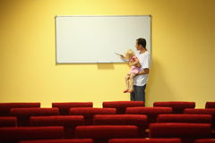 Father and little girl in empty presentation hall Stock Photos