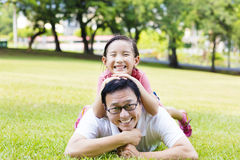 father and little girl lying on the grass Royalty Free Stock Images