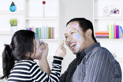 Father and little girl with painted face Stock Images