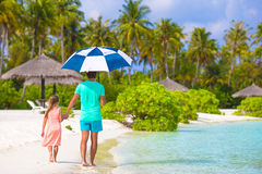 Father and little girl with umbrella hiding from Stock Photos